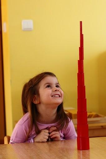 Dziewczynka patrzy na szczyt wieży z czerwonych klocków