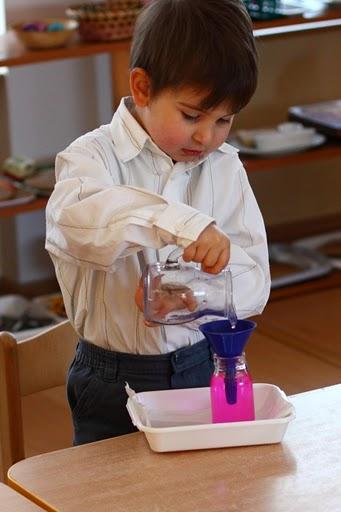 Chłopiec przelewa różowy płyn z dzbanka do słoika przez lejek